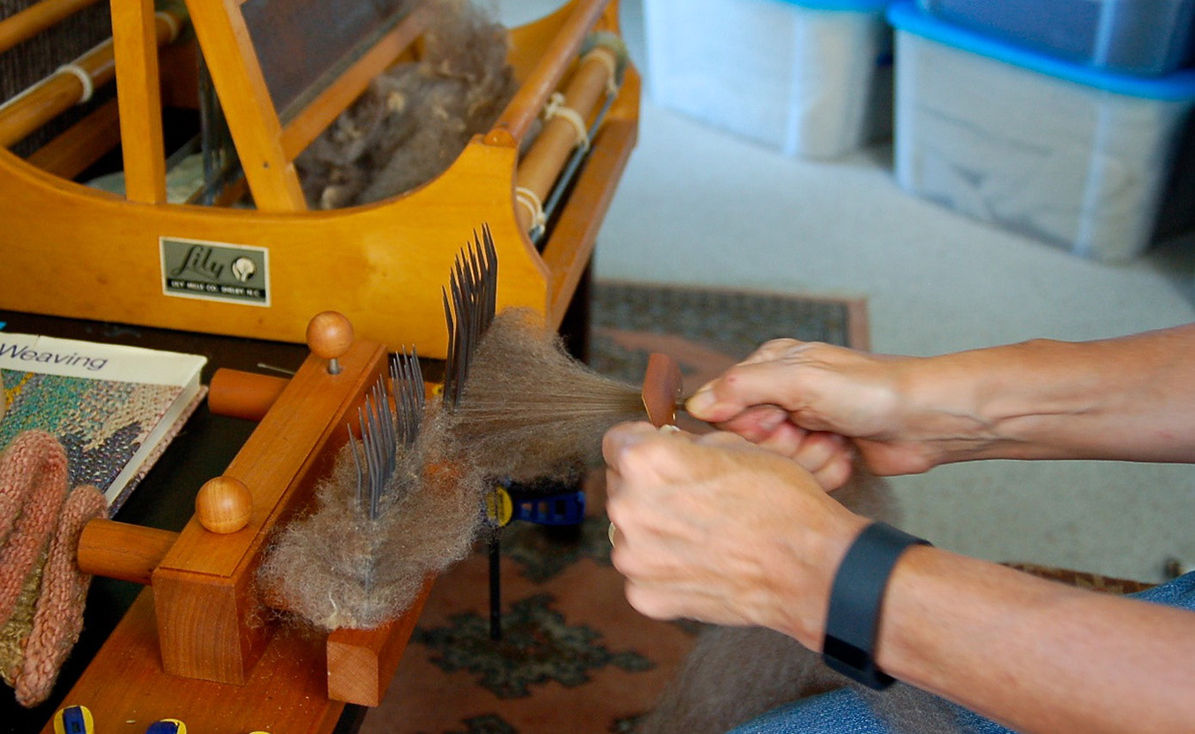 "Whitney combs the fleece with sharp mettle tines to sift out debris and align the strands of fiber in a single direction. She then pulls the ""combed top"" through a small hole to create roving, which can then be spun into yarn. 
