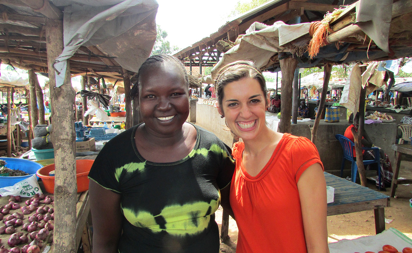 Theresa, right, and Mary, her language helper, next to Mary's booth at the Mundri market.   Photo by Will and Theresa Reed