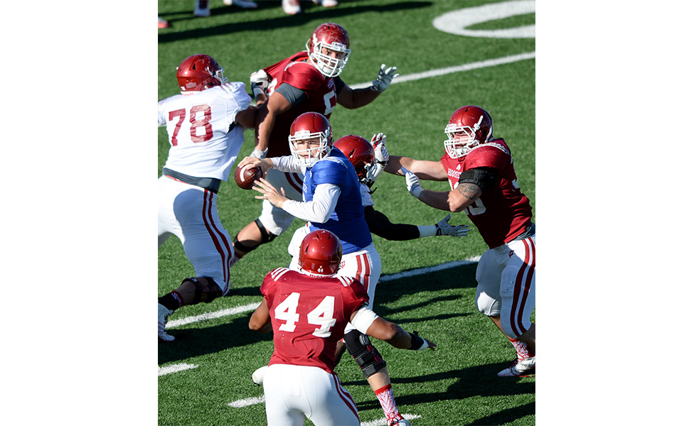 """The defense closes in on quarterback Nate Sudfeld during practice. Mangieri says nine-on-nine passing drills helped the defensive front line to start """"disrupting the quarterback.""""   Photo by Mike Dickbernd"""