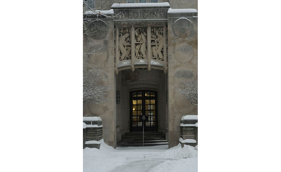 I've always loved the relief above the door at the former Indiana University School of Medicine building (now Myers Hall), and it looked so elegant framed in snow and with the warm light inside. | Photo by Ann Georgescu