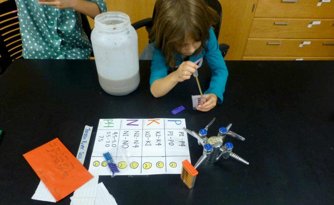 A young Saturday Science Quest student experiments with soil samples from Jordan River. | Courtesy photo