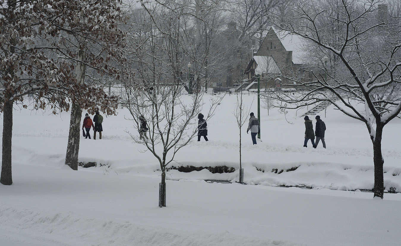 People walk, going along their business as usual despite the snow, through Dunn Meadow between Jordan River and East 7th Street. | Photo by Ann Georgescu