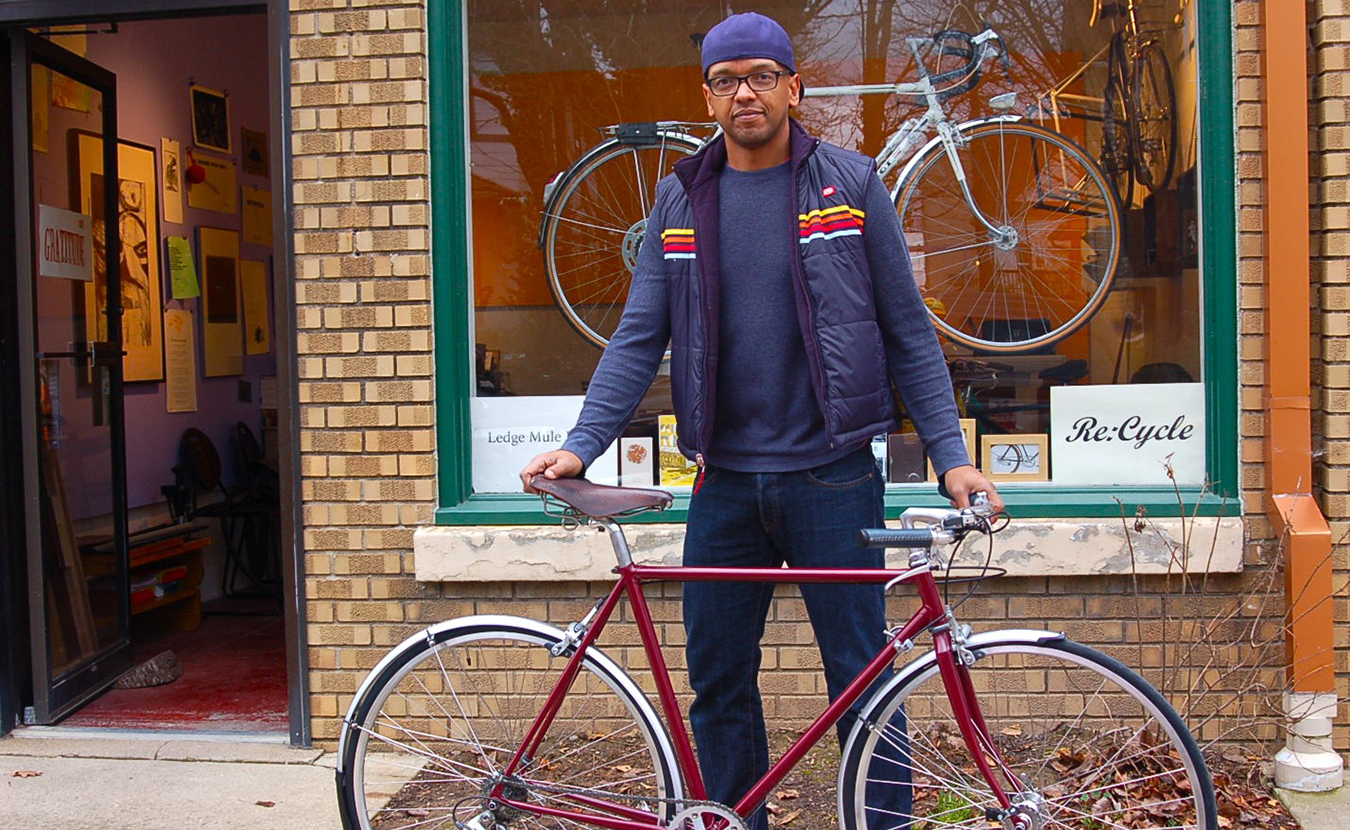 Wright with Welsch's refurbished bike — from a rusty, old road bike to a sleek, new city bike — outside of his storefront, Re:Cycle, in the I. Fell building at West 4th and South Rogers streets. | Photo by Sam Sveen