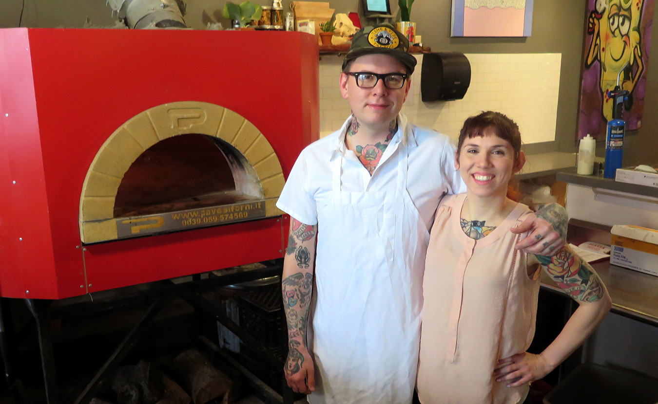 Adam (left) and Alicia Sweet, owners of King Dough pizza, stand next to their Italian brick oven in their brick-and-mortar location on the downtown Square. | Photo by Lynae Sowinski