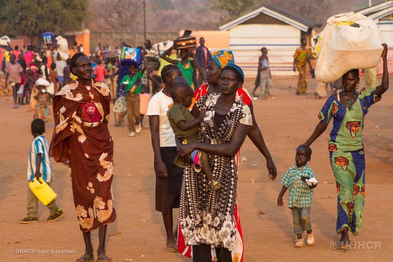 Newly arrived South Sudanese refugees carry their belongings at the Nyumanzi reception center in Adjumani, a district in northern Uganda. Since the first week of January 2016, Uganda has seen an influx of 4,587 refugees from the neighboring war-torn country of South Sudan. | Photo courtesy © UNHCR/Isaac Kasamani