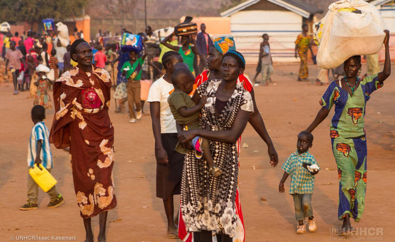 Newly arrived South Sudanese refugees carry their belongings at the Nyumanzi reception center in the northern district of Uganda, Adjumani. Since the first week of January 2016, Uganda has seen an influx of 4,587 refugees from the neighboring war torn country of South Sudan. | Photo courtesy © UNHCR/Isaac Kasamani