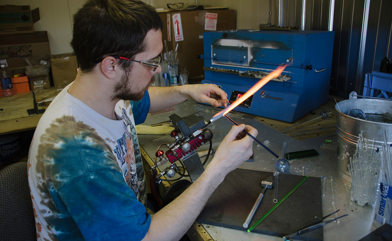 "Max ""Rowdy"" Van Deneede, owner of Rowdy Glass Company, working in his studio. 