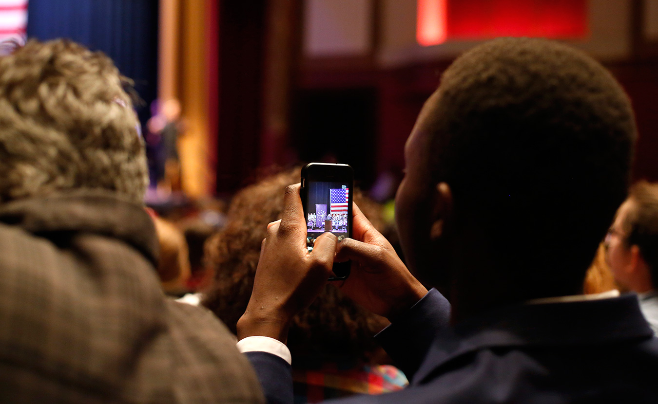 Stanley Njuguna, an IU freshman and a social media executive with IU Students for Bernie Sanders, captures the event on his phone. | Photo by TJ Jaeger