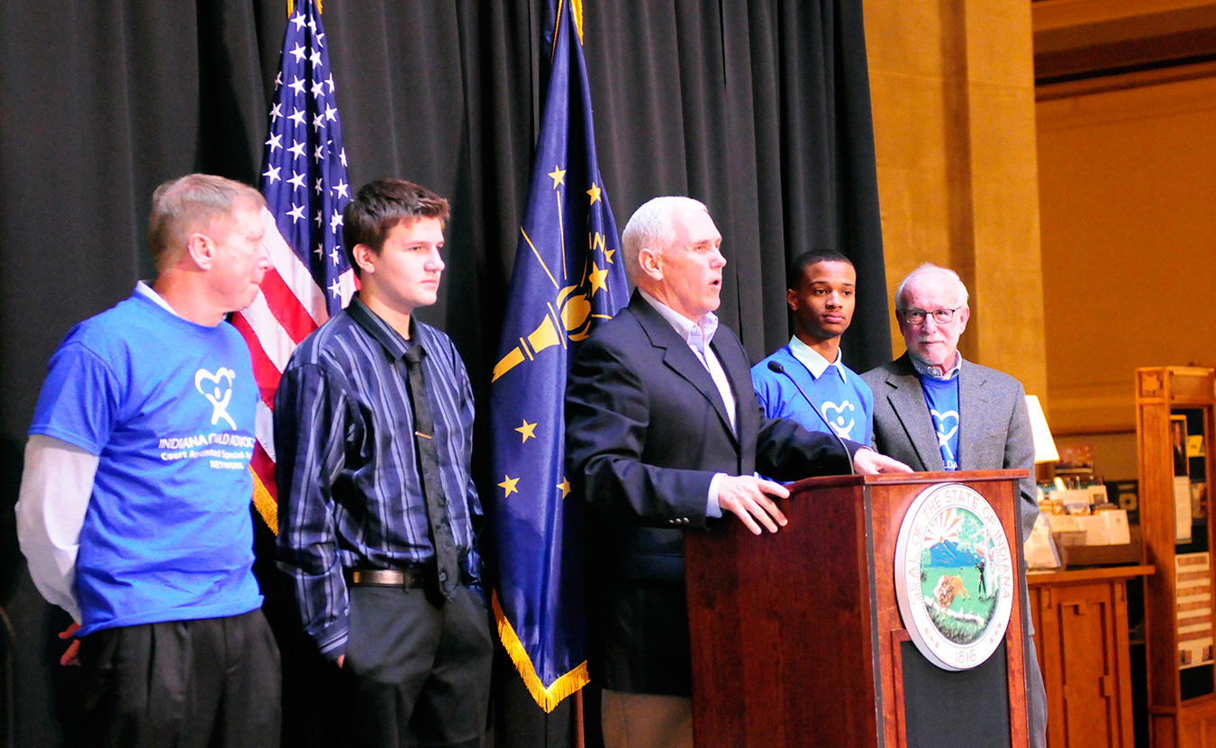 Phillips (second from right) and Shelton (right) stand on stage with Governor Mike Pence (center) at the CASA Day rally. | Photo by Ann Georgescu