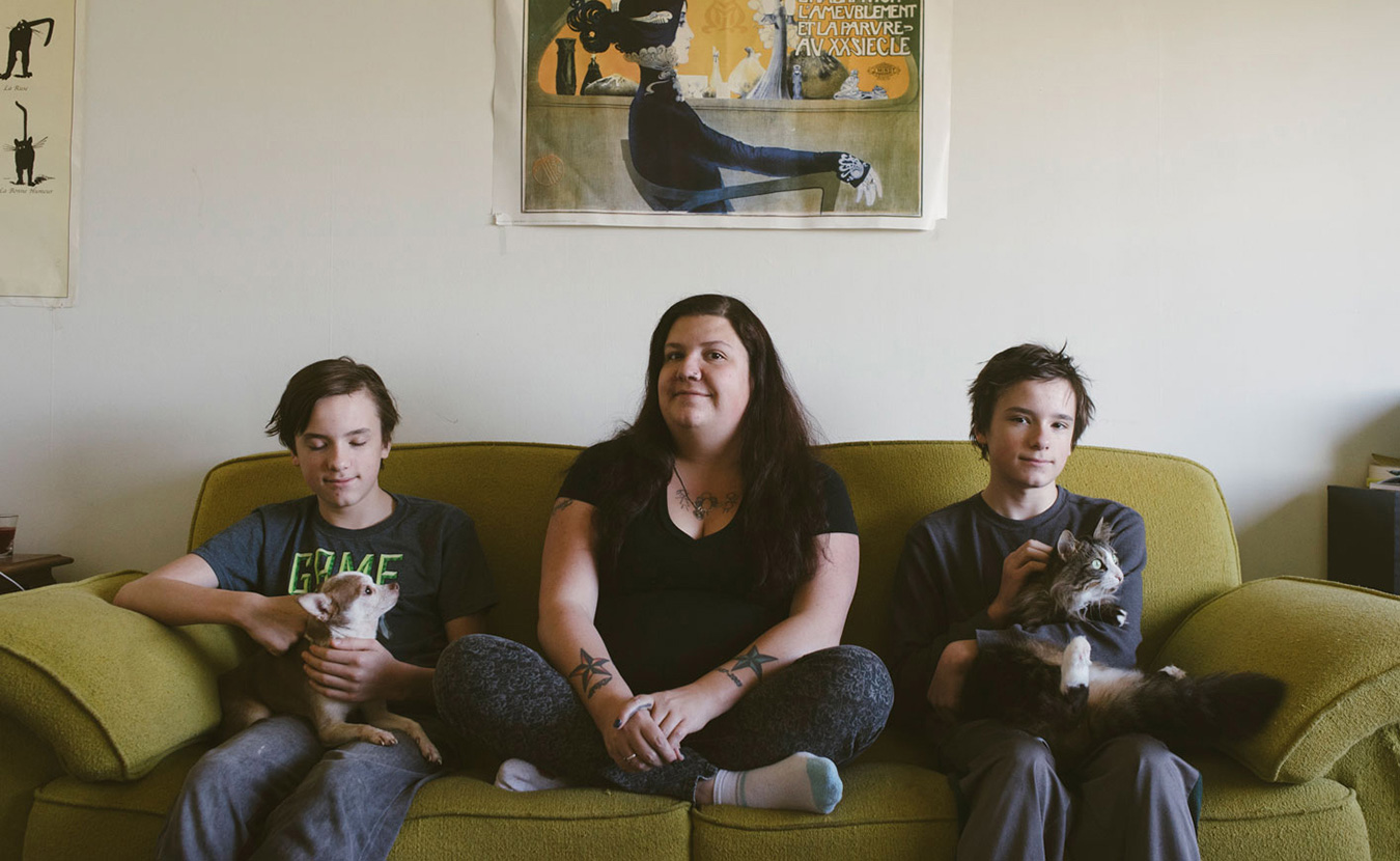 Laura Reagan sits with her twin sons, Korbyn (left) and Jarek, and their dog, Sancho, and cat, Squishy. Reagan has dealt with food insecurity on and off throughout her entire life and has worked very hard to protect her sons from the stress of being food insecure. | Photo by Natasha Komoda