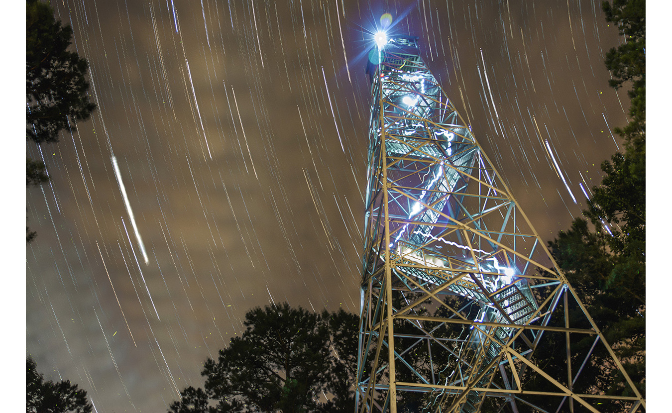 Clark set up his camera for a time lapse at the bottom of the Charles C. Deam Wilderness Area fire tower. After it was complete, he stacked 175 images and blended them using a program called StarStaX. The light from his head lamp was also caught in the pictures as he climbed to the top. | Photo by Nathan Clark
