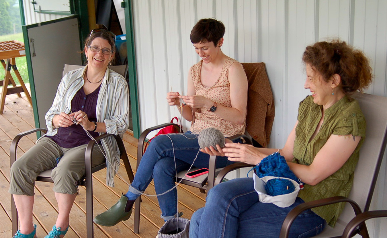 Lindsay (center) shares a laugh with fellow knitters, Faith Hawkins (left) and Karen Ellis, as they try out the Marble Hill Farm yarn for the first time. | Photo by Samuel Welsch Sveen