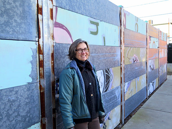 Cynthia Brubaker standing with the fence at Middle Way House. | Limestone Post