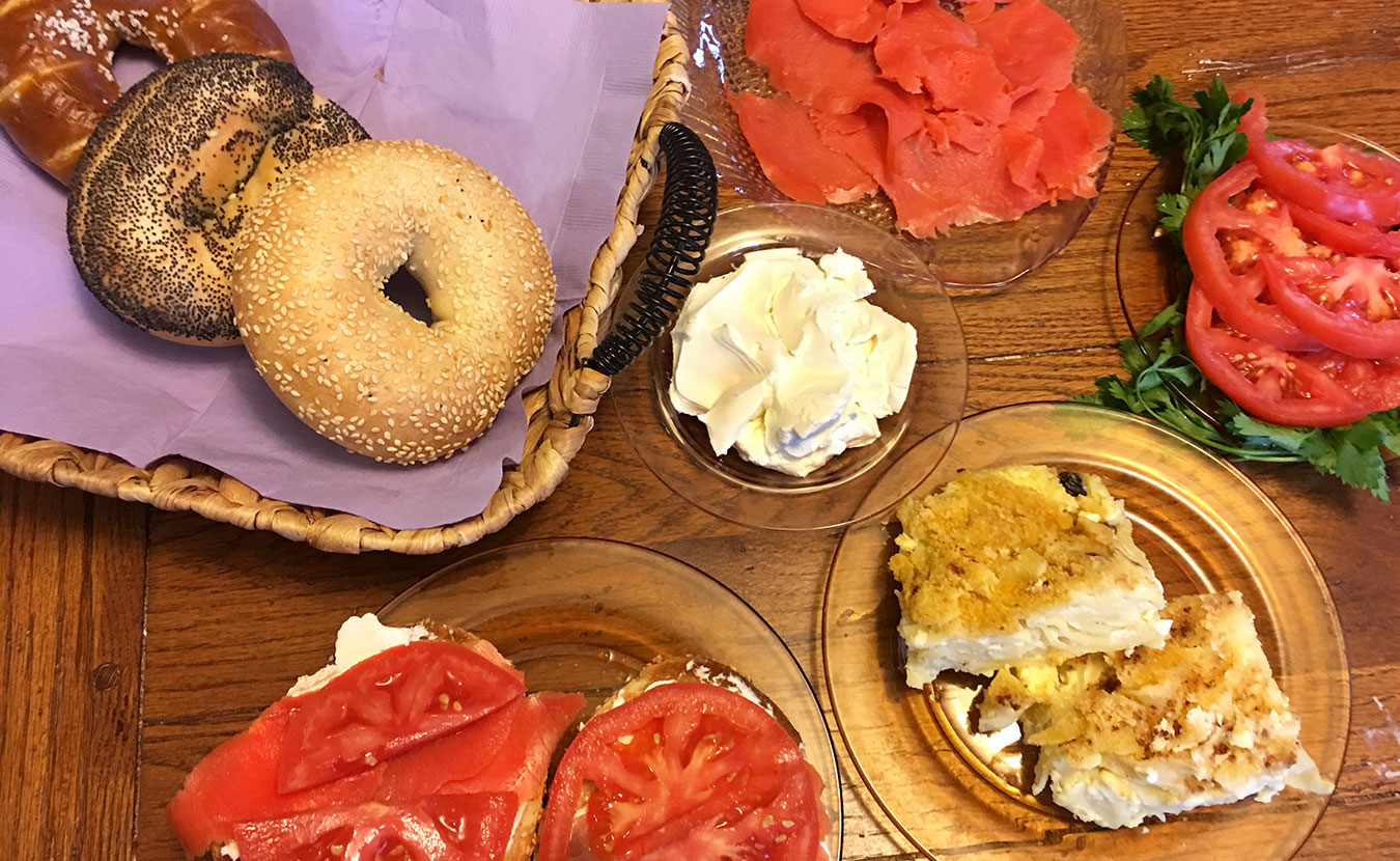 "Ruthie Cohen says Jewish soul food ""tastes like home."" Foods pictured here include (clockwise from top left) bagels, cream cheese, lox, tomatoes, kugel, and a hearty sandwich. 