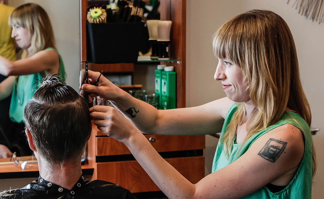 "Cathleen Paquet, a hairstylist at Hairstream Studio, styles a client's hair. She says this trade allows her ""to connect with other people really deeply."" 