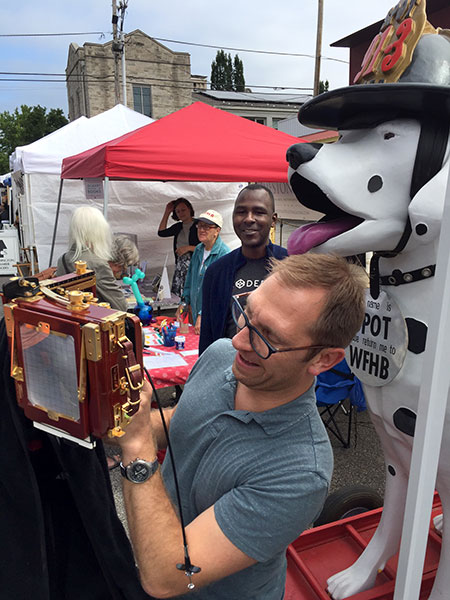Photographer Adam Reynolds sets up a photo at the 4th Street Festival of the Arts and Crafts as Ron Bronson looks on from the WFHB table. | Limestone Post