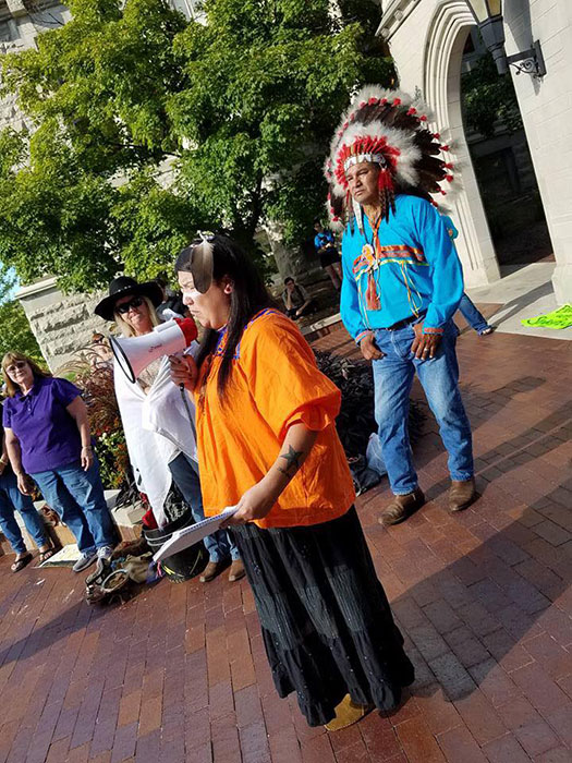 Writer Laura Martinez, wearing traditional Apache dress, speaks to a group of people at Sample Gates. As Halloween approaches, consider if your costume appropriates another's culture. | Courtesy photo