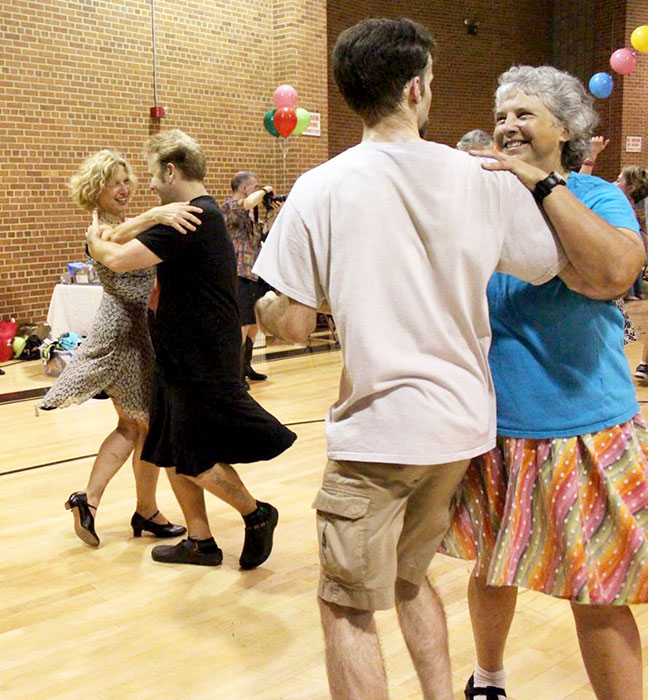 """Cathy Meyer, right, the board chair of Bloomington Old-Time Music & Dance, says the physical contact with others that comes with contra dance is what makes it """"a lot of fun."""" 