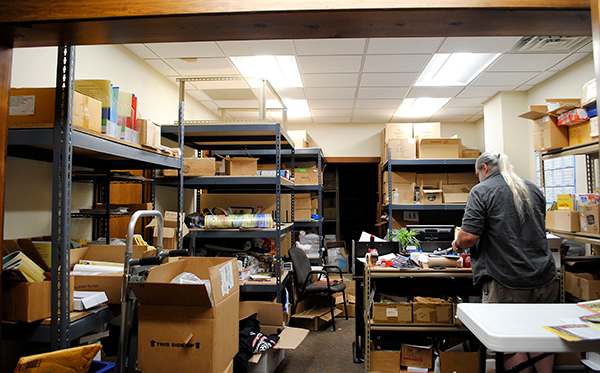 Jerry Iverson, The Language Conservancy's customer support representative, sifts through boxes of booklets, DVDs, flashcards, and other materials produced at the business's Bloomington headquarters.