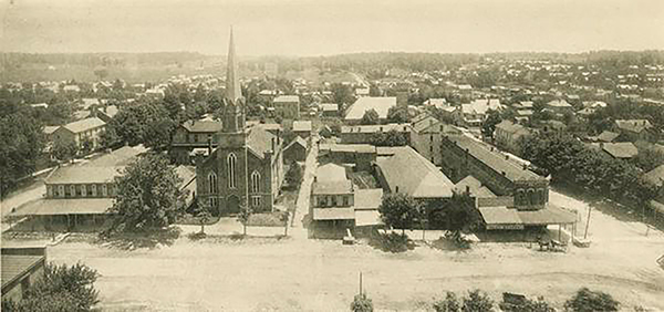"The east side of the downtown Square in 1891. The Indiana University Archives has labeled the buildings from left to right: ""Faulkner House Hotel (at corner with covered sidewalk); meat market (behind tree); First Presbyterian Church; alley; bakery, barber shop; feed store ?; J. H. Kirby's Meat Market; grocery store (the tall white building behind the grocery store is the old National House Hotel at 113 thru 121 East Kirkwood. In later years this hotel became the Grundy Hotel and the Hotel Kirkwood)."" 