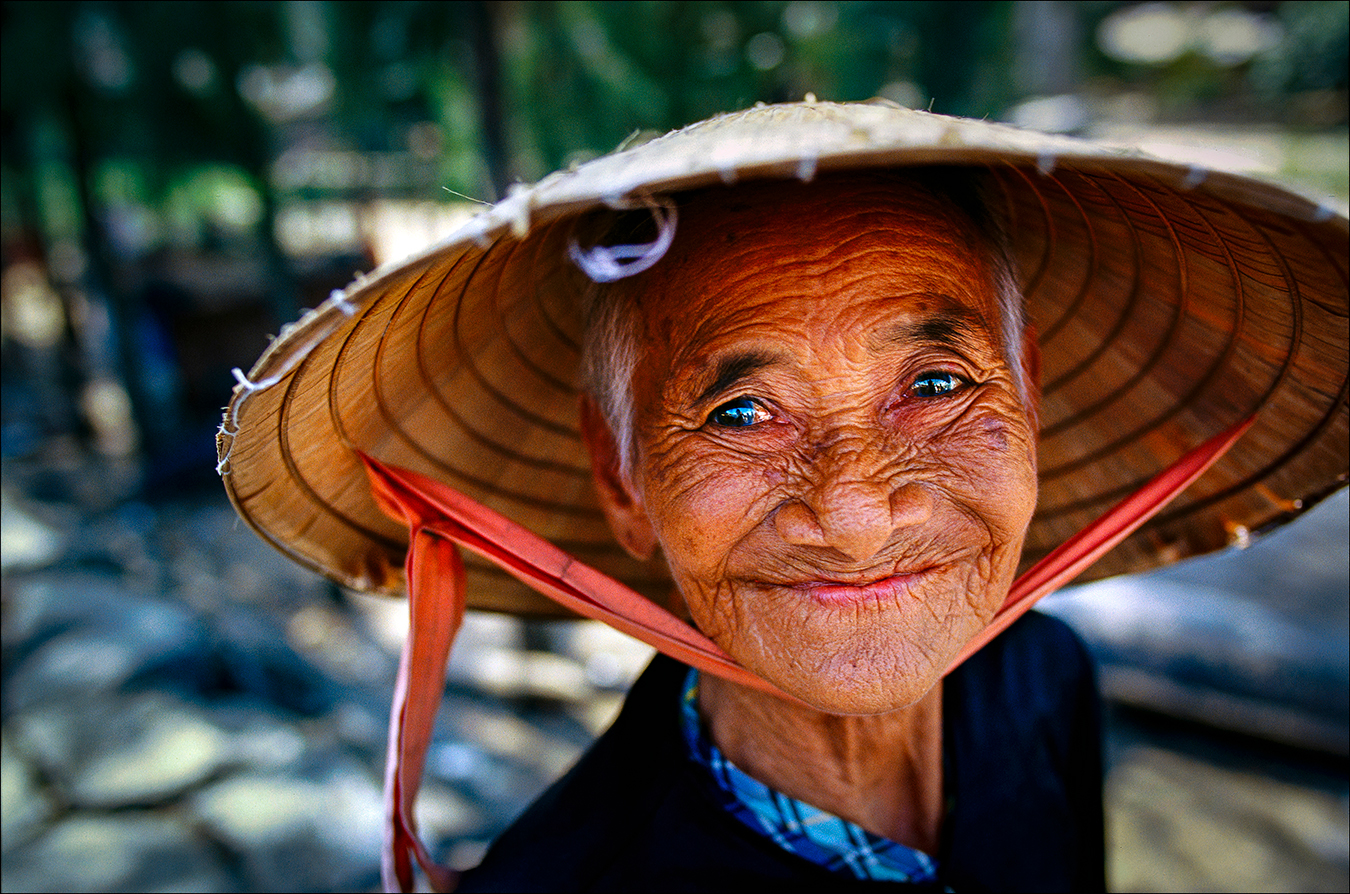 Despite living through years of hardship under the French, the Americans and their Vietnamese allies, and, more recently, conflicts with China, a vendor in a market in the coastal city of Hoi An has a ready smile for customers. She wears the nón lá — a conical hat made of palm leaf and worn by Vietnamese of all ages and both genders. | © Steve Raymer / National Geographic Creative
