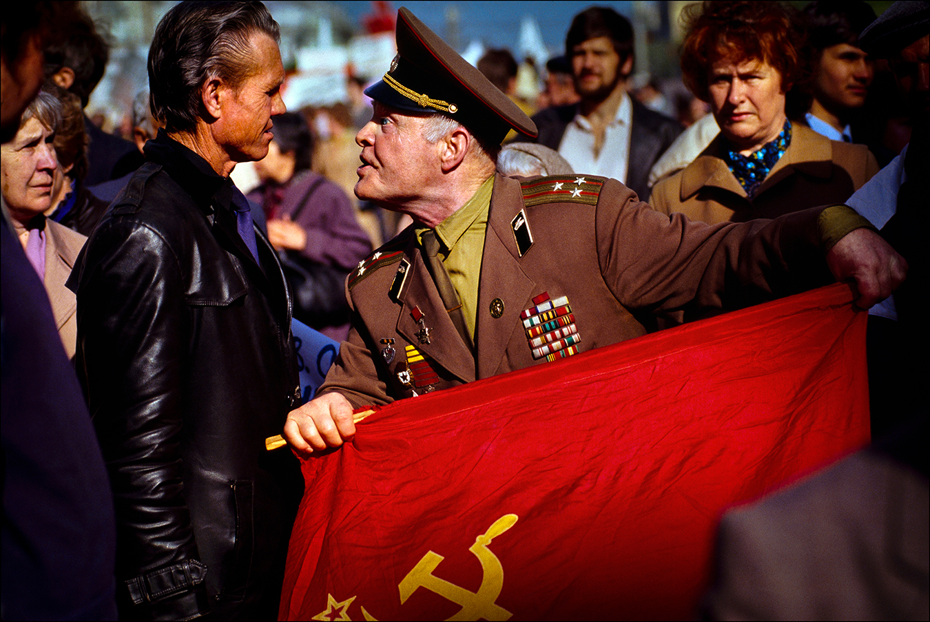 "Shouting ""traitor,"" a flag-waving colonel of the Soviet Army confronts a pro-democracy demonstrator at a May Day parade on Red Square in 1990. Hundreds of thousands of Soviet citizens turned a working-class holiday into an angry display of popular discontent with communist rule — a movement that would lead to the dissolution of the Soviet Union in December 1991. 