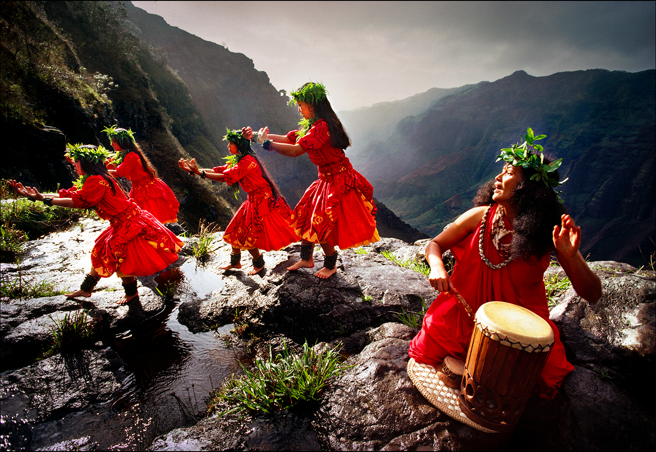 Performing the hula kahiko, or ancient Hawaiian hula, dancers blend simple footwork with hand gestures to illustrate the myths and histories of their families on the rim of the Waimea Canyon on Kauai. | © Steve Raymer / National Geographic Creative