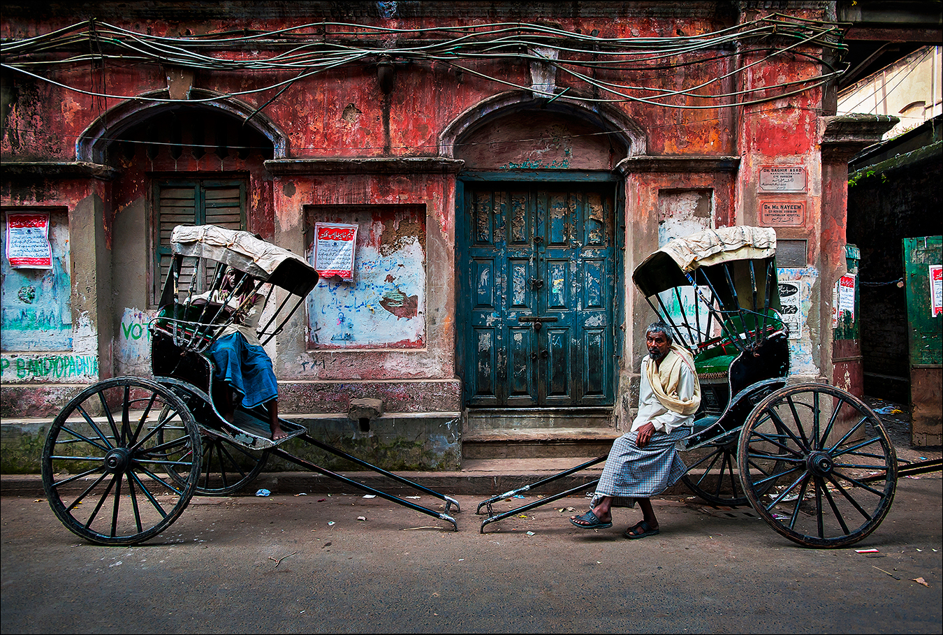 "As if in a scene from the early twentieth century, rickshaw-pullers rest on a backstreet in Calcutta, now renamed Kolkata, capital of the Indian state of West Bengal. The city's some six thousand licensed rickshaw drivers are often called ""human horses"" and generally earn less than five dollars a day navigating the city's crowded and sometimes flooded streets. 