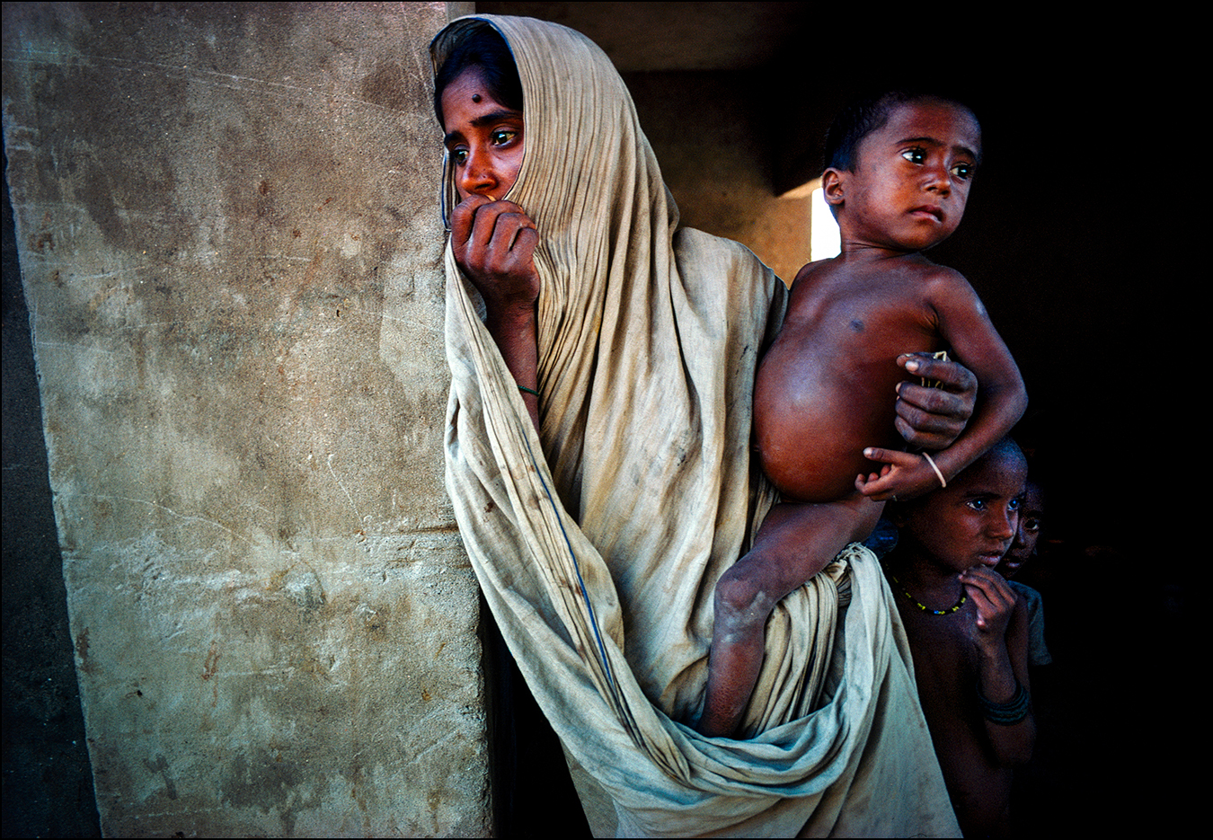 "Ration card clutched in her left hand, a mother waits with her three hungry children for powdered milk donated by the United States and Canada and dispensed by the Dutch Red Cross — another mind-numbing scene in Bangladesh during the 1974 famine. International relief experts called Bangladesh the most underfed and overcrowded nation in the world, while The New York Times reported, ""Mass hunger and starvation is no longer a threat. It is here."" 