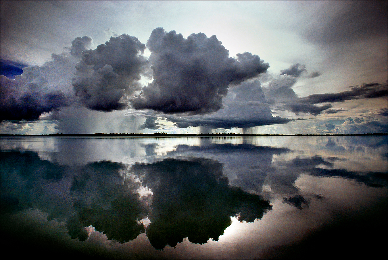 "Menacing cumulus clouds are mirrored in the placid waters of Lake Murray, the largest lake in Papua New Guinea, covering an area of some seven hundred square miles. About five thousand indigenous communities inhabit this lake region. In 1923, The New York Times reported on an Australian expedition that used amphibious airplanes to chart Lake Murray and the explorers' close encounters with indigenous people called, at the time, ""head-hunters."" 