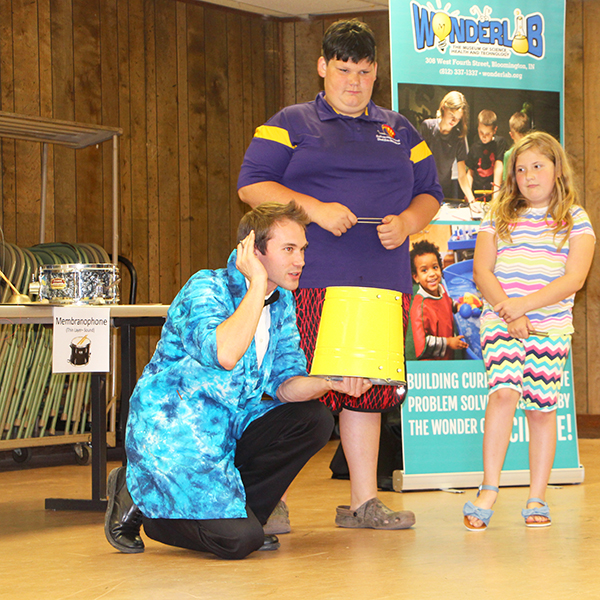For many students in rural areas of Indiana, STEM learning fades as the school year ends, writes Patti Danner. But a variety of programs are bringing STEM access to rural areas. For example, pictured here is Bloomington's Wonderlab Museum Educator Nick Whites as he demonstrates sound principles with audience assistants Fred Harvey, left, and Esse Harvey during his June Symphony of Science outreach program in Shelburn. | Photo by Patti Danner
