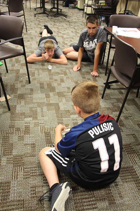 (Clockwise from upper left) Brayton Yoder, Dominic Wilson, and Brady Taylor created a device that launched a Ping Pong ball into a cup with precision at a Crane STEM Camp in June. | Photo by Patti Danner