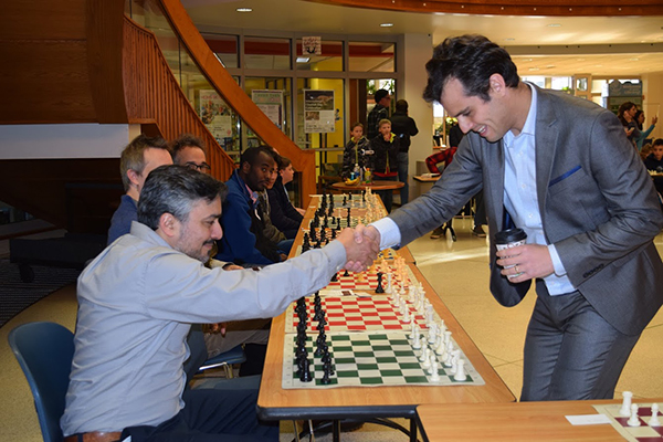 Medina, left, shakes hands with grandmaster Fidel Corrales, who visited Bloomington and played a simul game in December 2017. | Courtesy photo