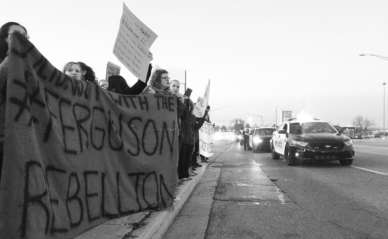 "How do people with similar values unite when their methods of action conflict with each other? Writer and organizer Alexandria Hollett says this question is illuminated by ""the difference between organizing campaigns on the one hand and symbolic activism on the other."" Pictured here on the east side of Bloomington in 2014 is a Black Lives Matter protest, in solidarity with protesters in Ferguson, Missouri. 