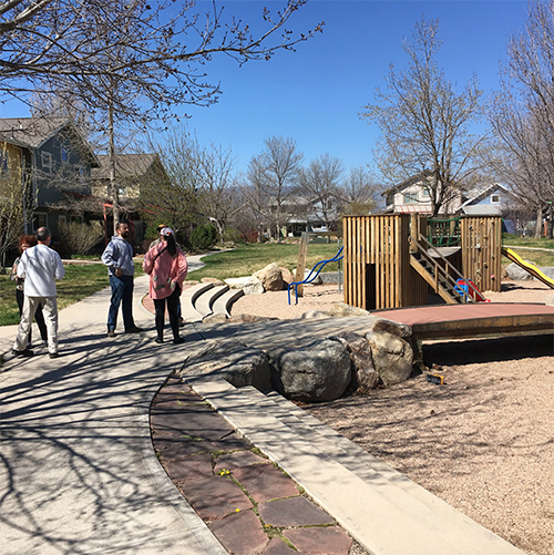 Wood, standing in center, speaks with residents on a common green path during a tour of Greyrock Commons in Fort Collins, Colorado. The Greyrock Commons design is similar to the planned design of the Bloomington Cohousing project. | Courtesy photo
