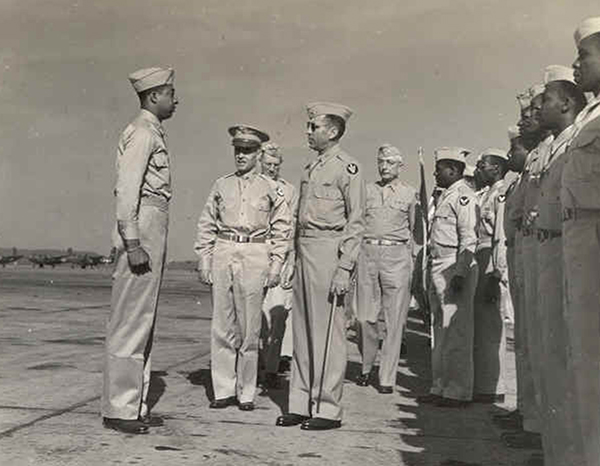 An official U.S. Army Air Forces photo of Colonel Robert R. Selway Jr. (center) reviewing the 618th Bomber Squadron, which is part of the 477th, at the Atterbury Army Air Field in Indiana on June 24, 1944. The Tuskegee Airman that Colonel Selway is facing is Hubert L. Jones. Selway would later segregate the officers's club by designating all black officers as trainees. | Public domain