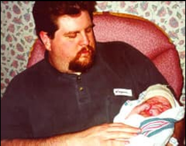 Troy sits with his newborn daughter. | Courtesy photo