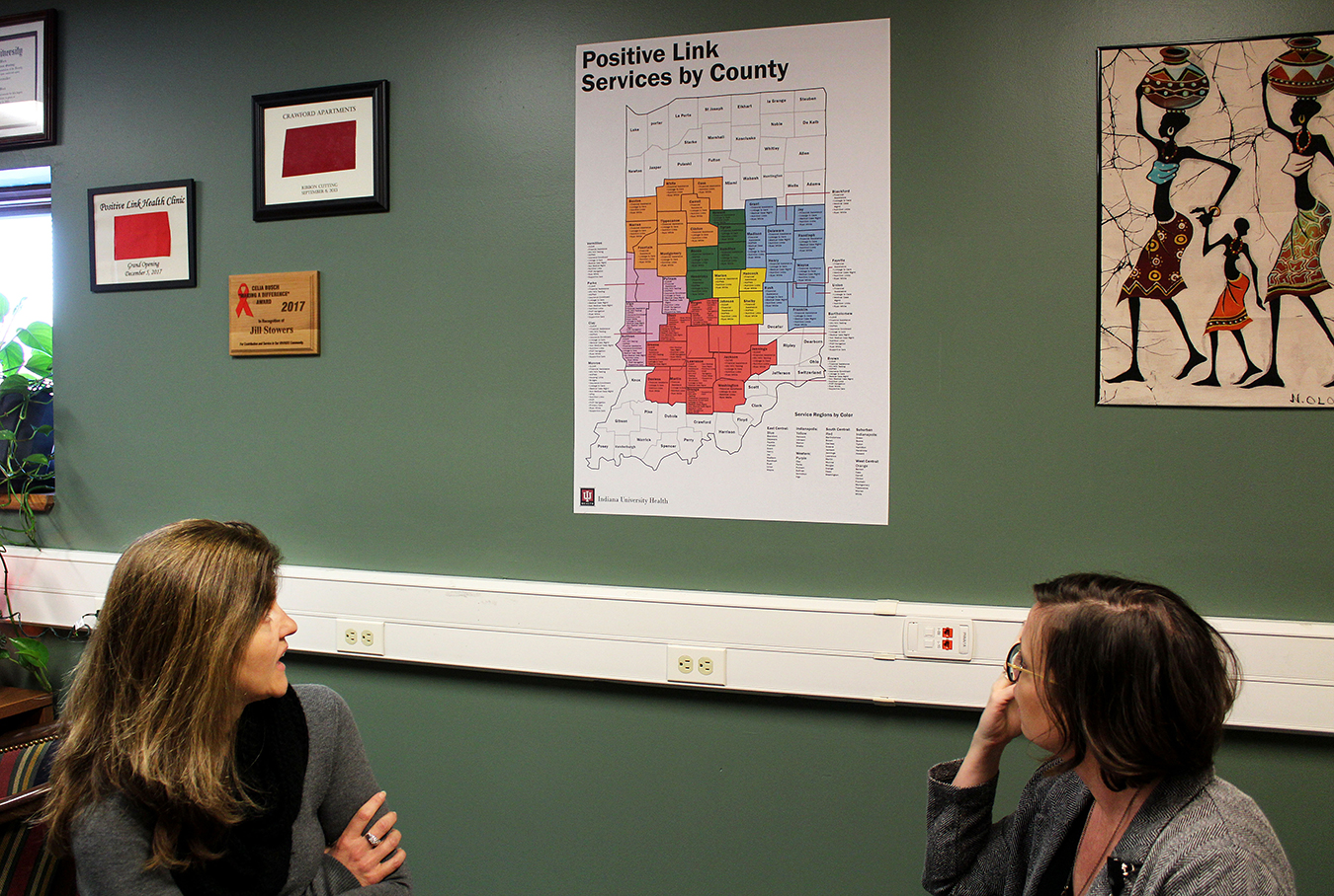 Baynes and Brinegar explain a map posted on their wall, which visualizes what Positive Link services are available to those who live in every county throughout Indiana. | Photo by Nicole McPheeters