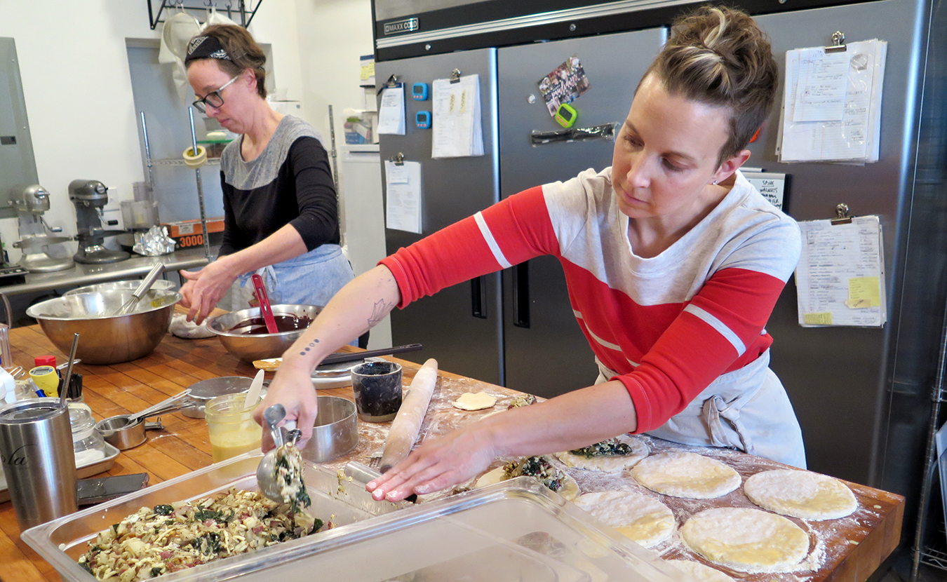 Jenson, left, and Armstrong — who are making peanut butter brownies and hand pies, respectively, in their bakery on South Washington Street — say that when they slow down and enjoy their food, they tend to feel more satisfied and sometimes eat less. | Limestone Post