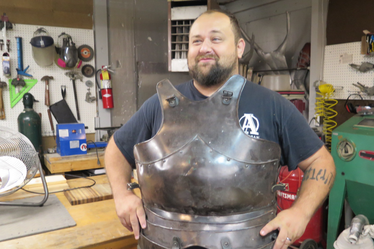 Adam Nahas in Burl and Ingot Tool Library showing a piece of armor that he made. The Tool Library is part of Artisan Alley, the collective art space, studio, workshop, computer lab, gallery, and other projects that began in Nahas's basement more than a decade ago. | Limestone Post