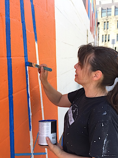 Eva Allen painted the mural 'Love This City' at the Mother Bear's Pizza east-side location last spring. She also painted 'You Belong Here' in Peoples Park in 2017 | Limestone Post