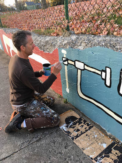Sam Bartlett renovating his mural at Building Trades Park on West 2nd Street. Painted in 2013, Bartlett's mural was the first of several murals commissioned by the city. | Photo by M.J. Bower