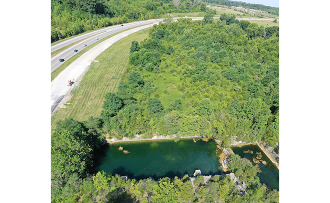 The view looking west along State Road 46. Long Hole (bottom) was a popular swimming hole for many longtime residents. A parking lot is proposed for the wooded area in the top right of the photo. | Photo by Geoff McKim
