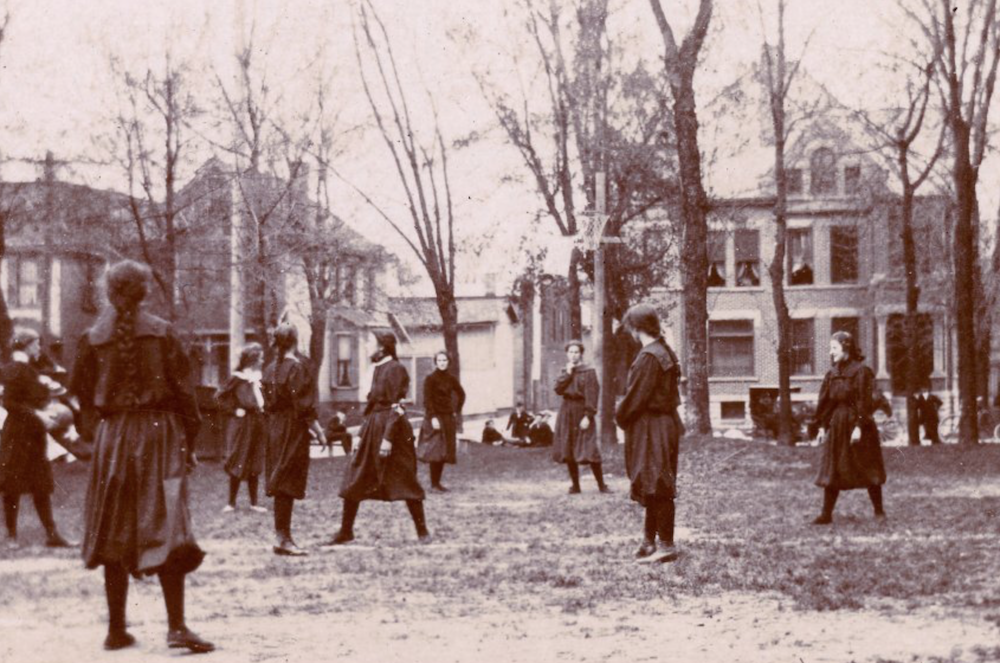 "This photo, taken on April 22, 1899, shows a high school girls' game between Shortridge High School and the Y.W.C.A. in Indianapolis. A hoop and net (without a backboard) can be seen slightly above and to the right of center. The ball handler is to the left. High school nicknames and mascots would not become widely used until the 1920s. The photo is titled 'Shortridge High School and Y. W. C. A. girls playing basketball, Indianapolis, Indiana, 1899' and provided courtesy of <a href=""http:indianaalbum.com"" target=""_blank"">IndianaAlbum.com</a> from the Nicolas Horn Collection."