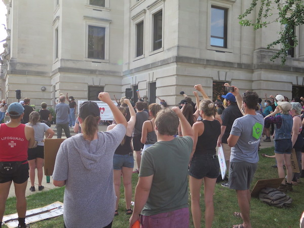 "During the protests, members of the crowd joined speakers in shouting ""No justice, no peace,"" ""Black Lives Matter,"" and the names of victims killed by police. 